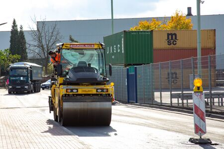 Andernach, Rhineland Palatinate, Germany - October 25,2019: vibration roller compactor at urban road construction and repairing asphalt pavement works with a truck and containers in the background 에디토리얼