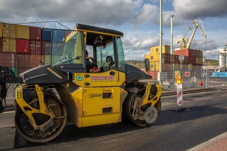 Andernach, Rhineland Palatinate, Germany - October 25,2019: vibration roller compactor at urban road construction and repairing asphalt pavement works with containers in the background