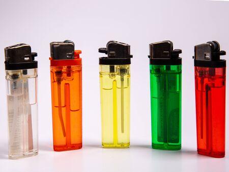 cinq briquets à gaz de différentes couleurs sur fond blanc