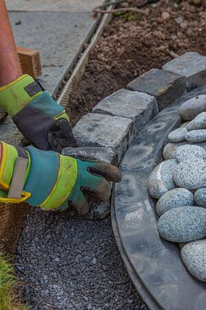 hands with work gloves arranging gritting material and basalt cobblestones into the curb of a garden fountain