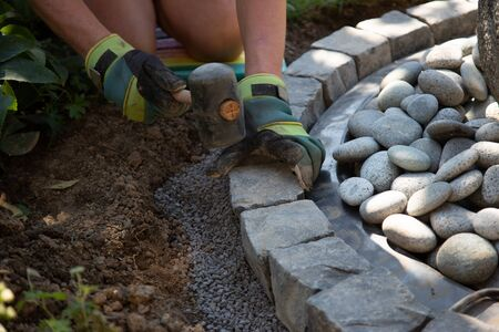 Parts of a hobby worker with work gloves arranging basalt cobblestones into the curb of a garden fountain