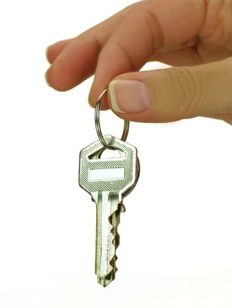 economic rent: Female hand holding key in front of a house  Stock Photo