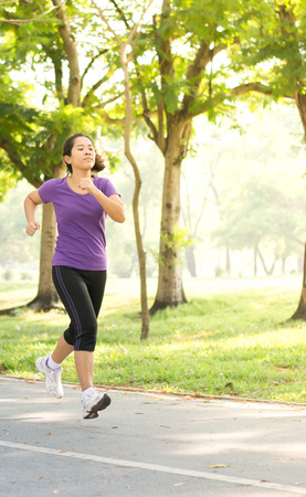 intend: Asian woman who interrest in better healthy is running in the garden with tree and grass in the morning with yellow sun light in relax feeling