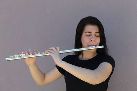 Black-haired girl plays the flute outside in front of a grey background closeup
