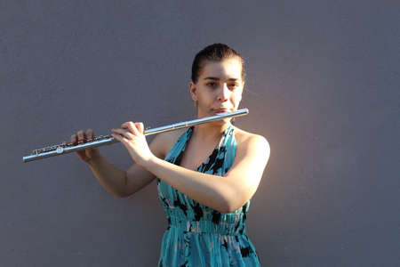 Girl plays the flute in front of a gray background