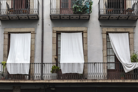 white curtains: BARCELONA,SPAIN-AUGUST 31,2015: Facade building detail balconies with white curtains in El Born quarter of Barcelona.