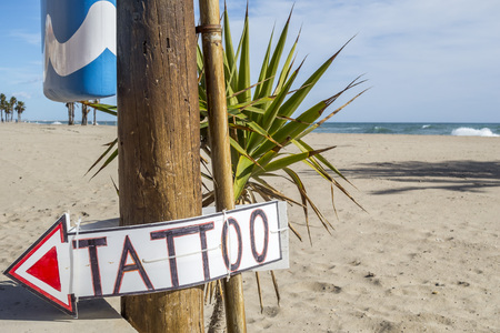 Mediterranean beach and tatoo sign.