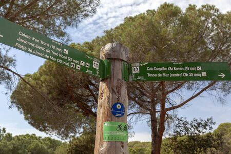LLORET DE MAR,SPAIN-APRIL 1,2019: Sign distance route between Lloret de Mar and Tossa de Mar, Costa Brava.