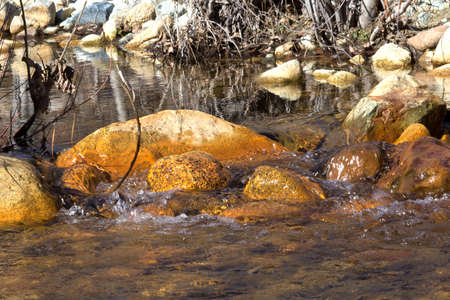 Water flowing over Orange Rocks Stock Photo