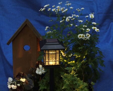 A solar lantern casts light on flowers and a fake birdhouse