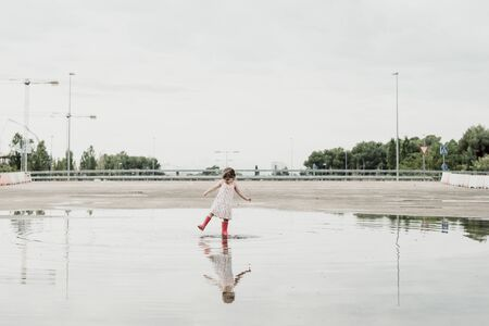 little girl playing in the puddle with the water boots, happy