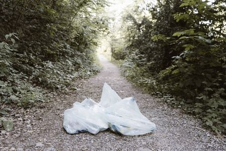 plastic and trash in the field with trash bag