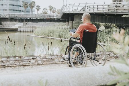 Thoughtful wheelchair man looking at a lake in the city Banco de Imagens