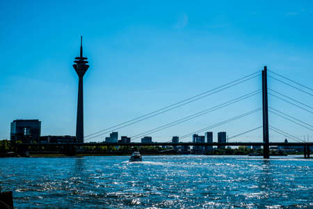 View of the Rheinkniebrücke bridge over the river and the Rhine Tower in Dusseldorf, Germany