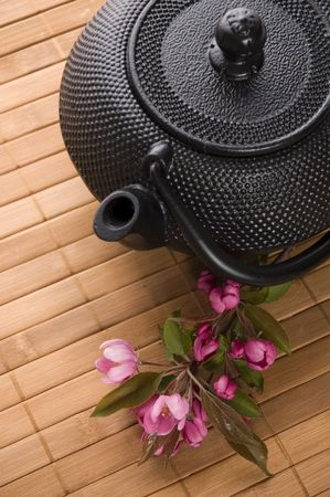 teapot with a fresh flowers on the bamboo tray photo
