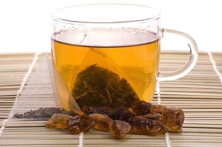 intense flavor: white tea, nylon tea-bag and golden sugar Stock Photo