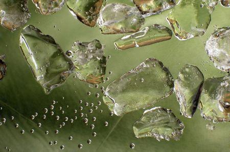 macro of ice cubes. fresh green background photo