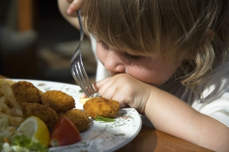 small plate: little girl eating french fries. dinner in a restaurant