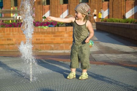 sweet girl playing in a public fountain. summer scenic. childhood photo