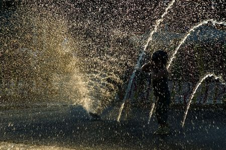 child playing in a public fountain. summer scenic photo