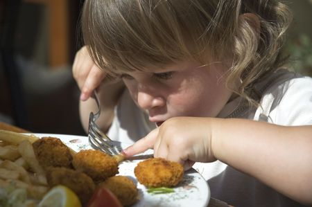 child food: little girl eating french fries. dinner in a restaurant