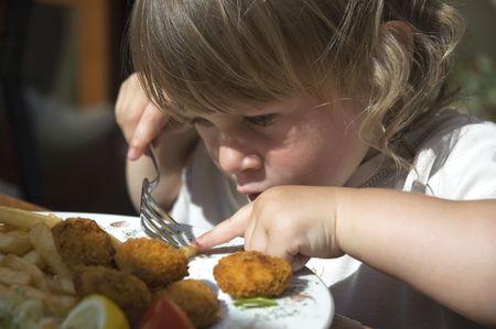 フライド ポテトを食べる少女。レストランでの夕食