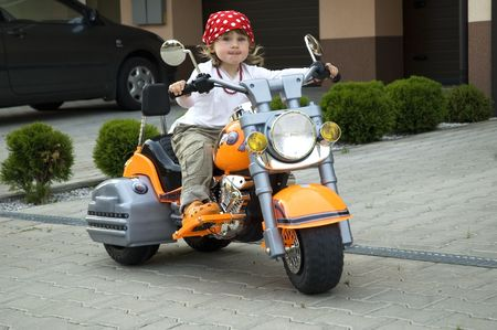 young girl on motor-bike on the playground