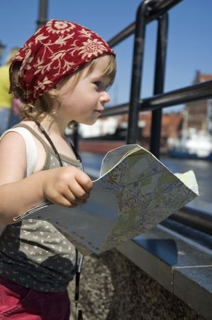 discover: little girl with a city map. Gdansk. Poland