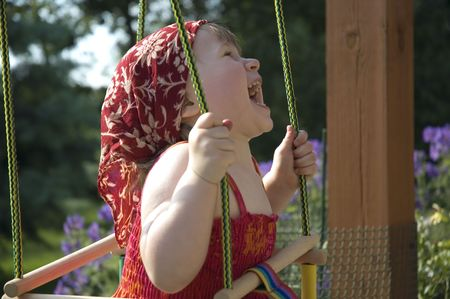 two-year-old girl on a swing in the garden photo