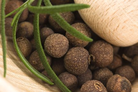 Mortar with fresh herbs and allspice berries photo