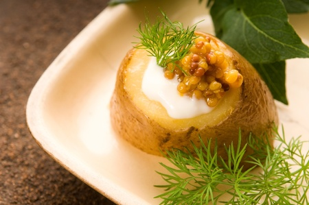 Baked potato with sour cream, grain Dijon mustard and herbs photo