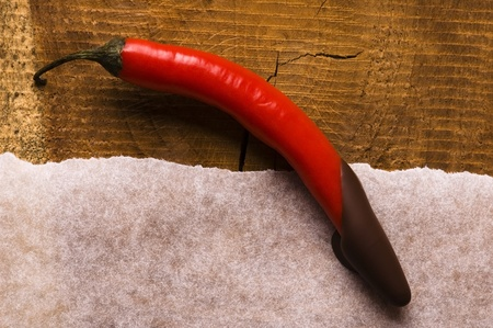Red hot chilli pepper with dark chocolate photo