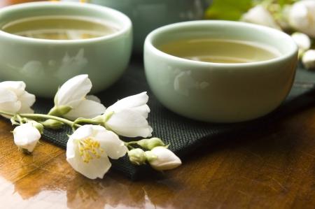 Grüner Tee mit Jasmin in der Tasse und Teekanne auf Holztisch Lizenzfreie Bilder