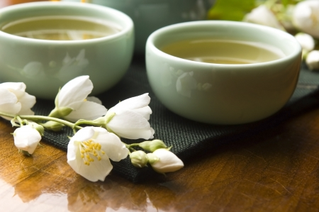 Green tea with jasmine in cup and teapot on wooden table photo