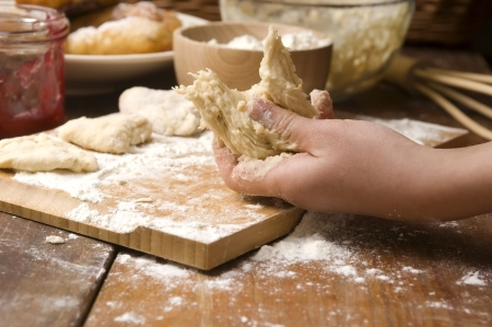 Detail of hands kneading dough photo