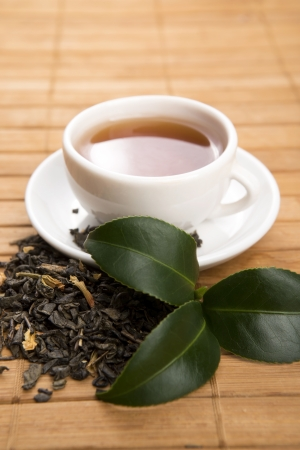intense flavor: A cup of green tea with freh leaves