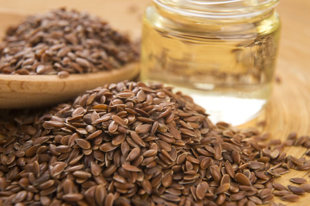 Linseed oil and flax seeds on wooden table  photo