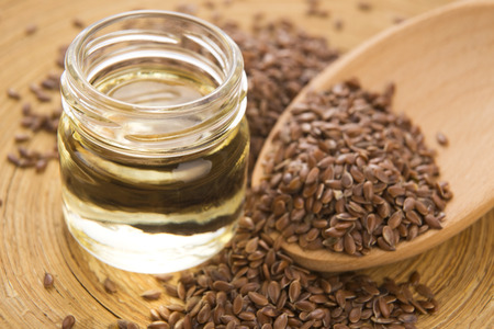 Linseed oil and flax seeds on wooden background  photo
