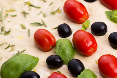 lingua: Focaccia with black olives, tomatoes and basil Stock Photo