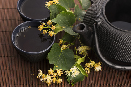 linden tea: teapot and cup with linden tea and flowers Stock Photo