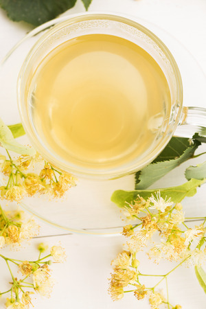 nontraditional: teapot and cup with linden tea and flowers Stock Photo