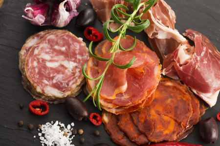 a pile of different spanish embutido, jamon, chorizo and lomo embuchado
