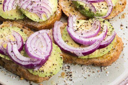 Sandwich with fresh avocado and onion on a plate Reklamní fotografie - 133483121