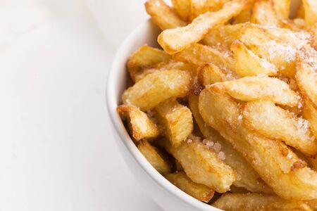 Tazón de fuente de patatas fritas sobre un fondo blanco. Foto de archivo