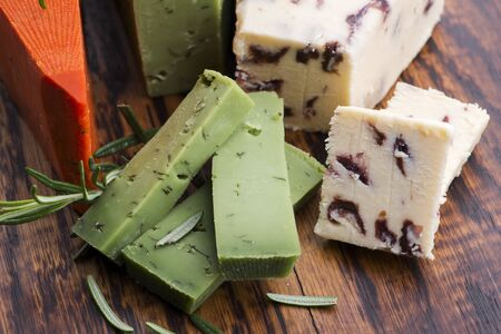 Different types of cheese are cut on a plate with rosemary Stock fotó