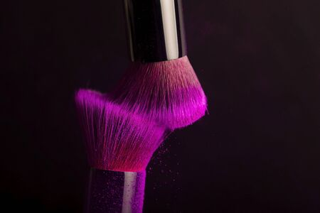 Cosmetics brush and colorful makeup powder