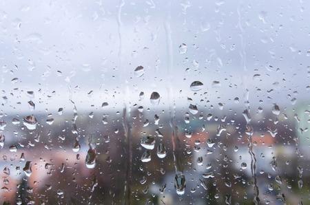 Rain drops on a window glass on a rainy day background