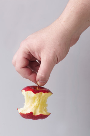 hand holding a red apple core by the stalk isolated on grey background