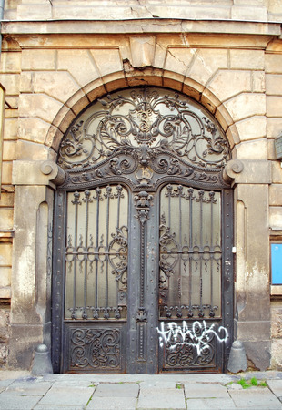 beautiful art nouveau door gate with iron flower motives and ugly graffiti Stock Photo