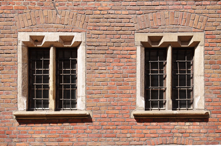 renaissance windows with bars in a red brick wall